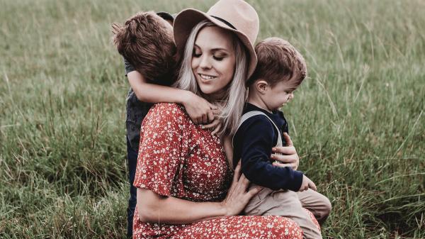 Eine Frau hockend mit zwei Kindern.